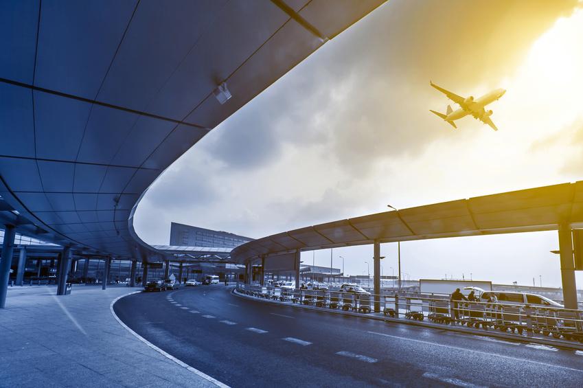 Bild eines Flughafen-Terminals mit einem Flugzeug am Himmel.