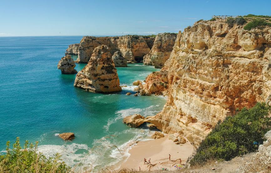 Algarve, steil abfallende Felsen an der Küstenlinie Portugals an einer kleinen Bucht am Atlantik