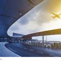 Flughafenterminal mit startendem Flugzeug bei Sonnenuntergang